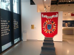 exhibition at mshed featuring modern guild banner in red