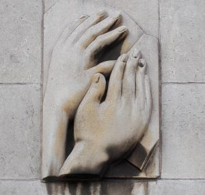 Relief showing hands reading braille on the side of the School's extension.
