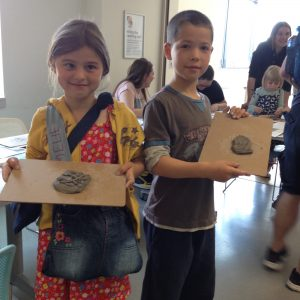 Children show off their clay artwork