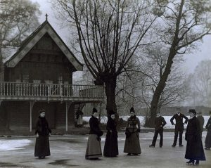 Men and women in Victorian dress on a frozen lake, alongside a building with a wooden balconyLan