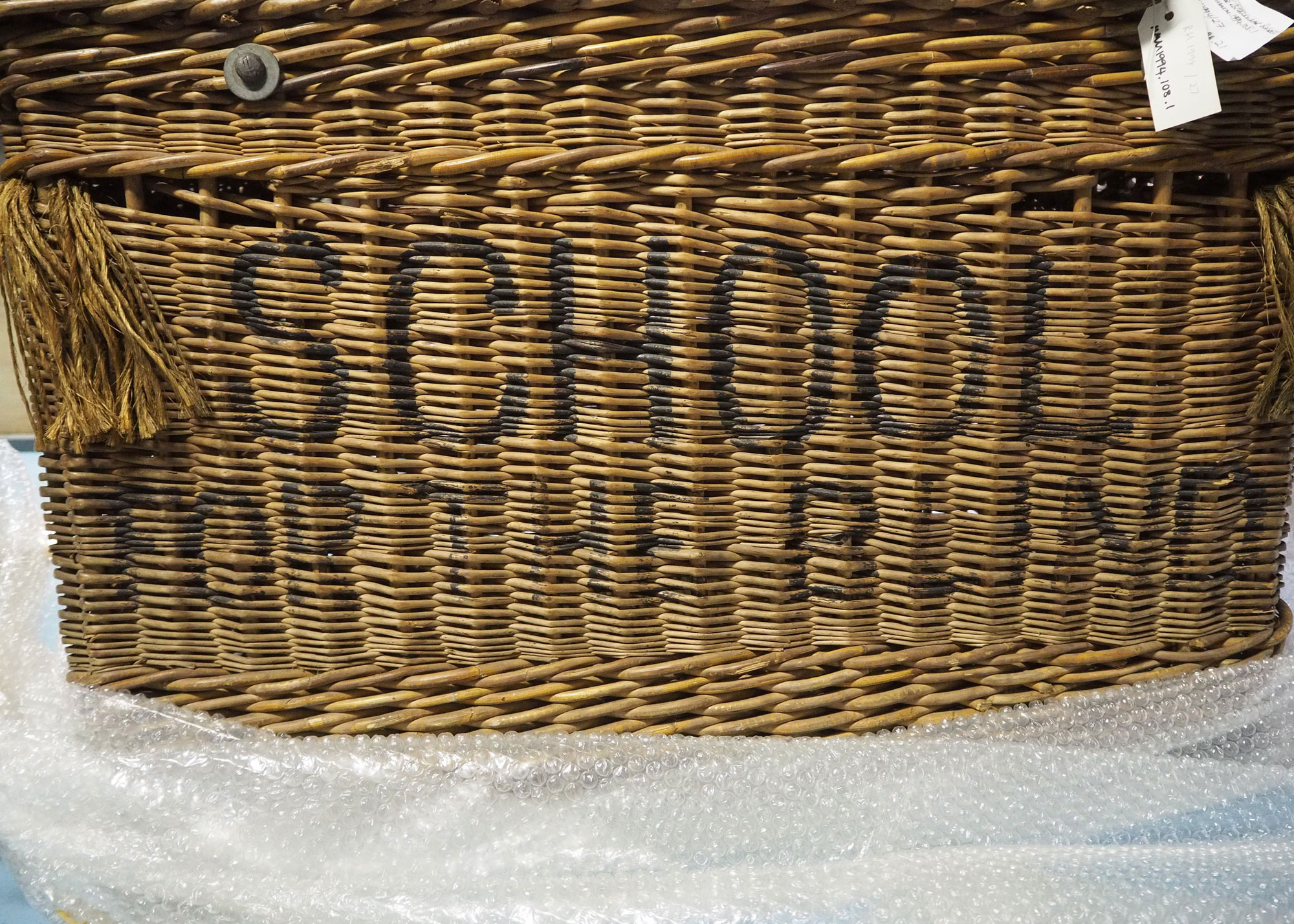 Large rectangular laundry basket with hinged lid and rope handles with 'School for the Blind' stencilled on the front. In the collection of the Museum of Liverpool MMM.1994.108.1, image taken by Anna Fairley Nielsson.