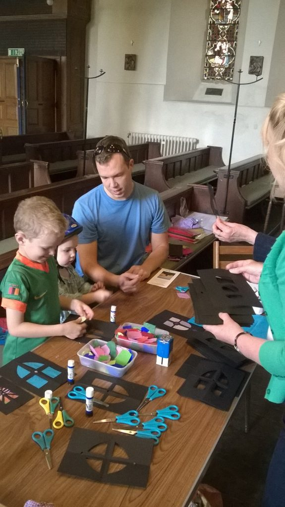 Children and adults use tissue paper and card to make stained glass windows