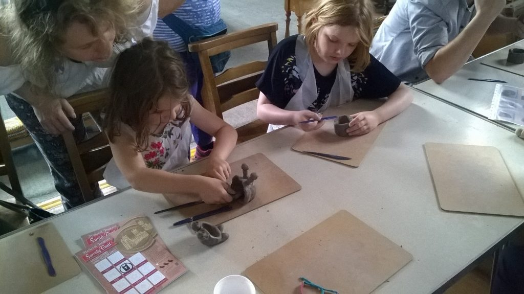 Two young girls craft objects out of clay