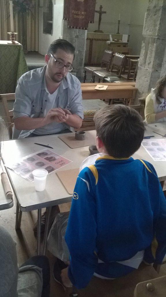 Man talks to child in church craft workshop