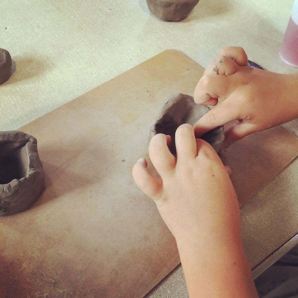 Child's hands make pinch bowl