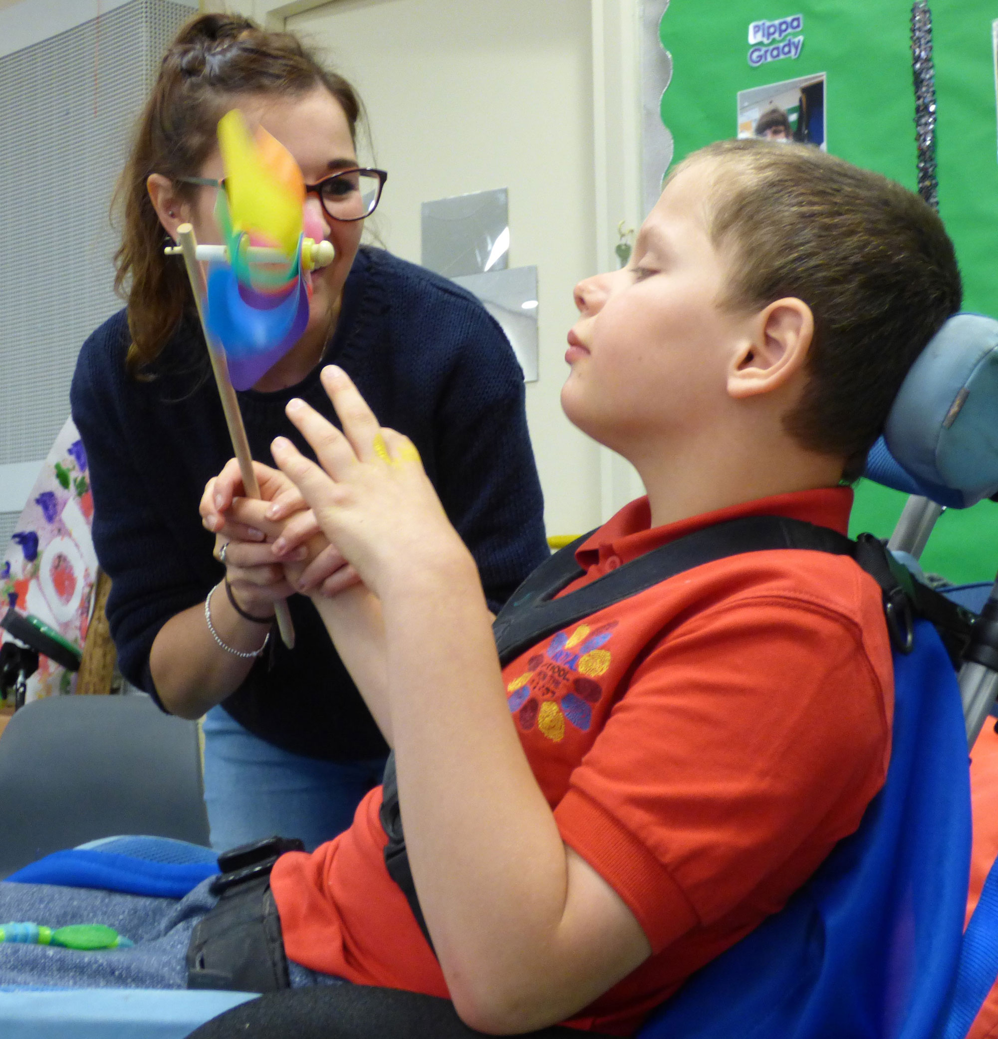 young boy listens to swirling handheld fan in workshop with woman