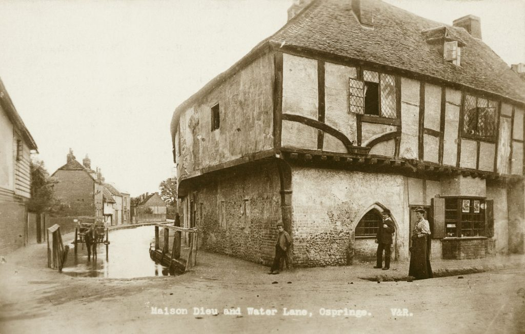Exterior view from the north-east showing a man and woman with a boy outside the Maison Dieu house, with a horse and cart standing in the stream to the left