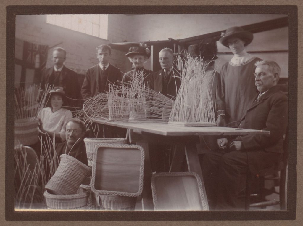 Image shows table with half weaved baskets, the completed items on the floor, and a group of weavers standing and sitting around the table.