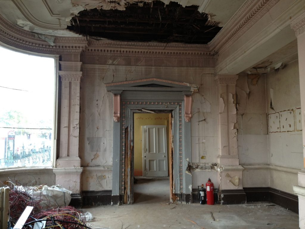 Crumbling paintwork on a grand interior with neoclassical scrollwork around a blue door.