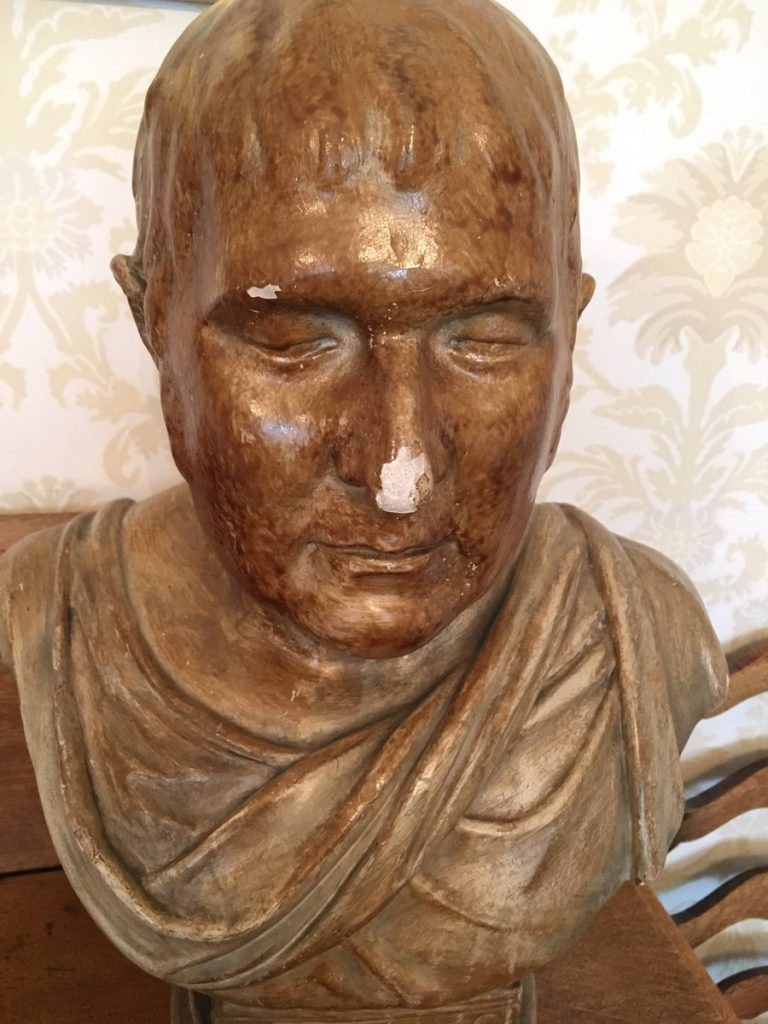 Image shows bust of man covered in gold and with Roman senator style cloth wrapped around his upper chest