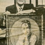 image shows man in business suit holding a portrait of Ada Vachell