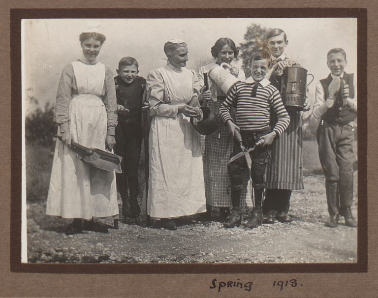Adults and children in the countryside posing with cleaning utensils