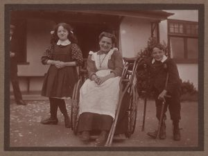 Woman in wheelchair, surrounded by girl and boy