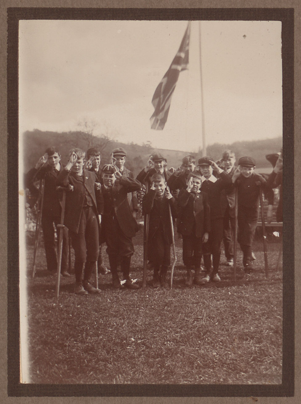 Boys in scout group stand in front of a union jack