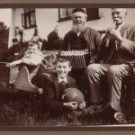 Old men with a whistle and accordion sit with two young boys with a football and wheelbarrow
