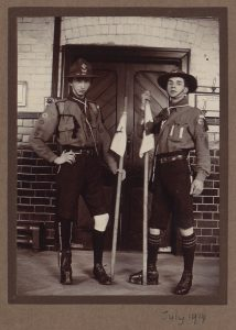 Two young men with scout uniforms and flags