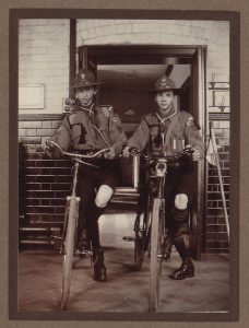 Two older teenagers with bicycles in scout uniforms