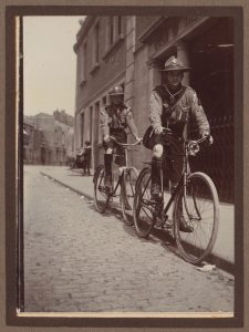 Two older scouts from the Guild on bicycles on a cobbled street