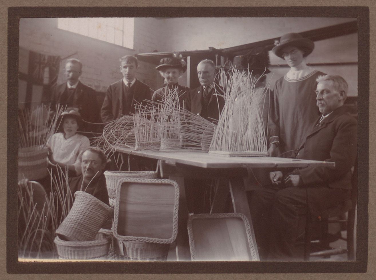 Ladies in hats and men in suits and ties sitting with woven baskets