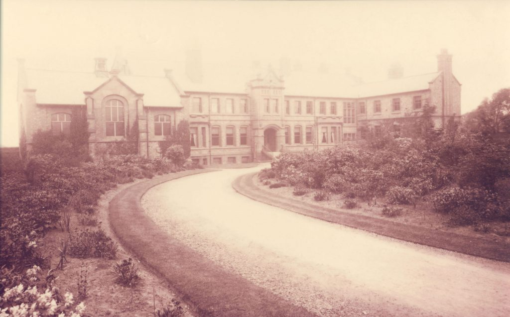Image shows slightly overexposed black and white photograph of a large Victorian building, with a sweeping drive surrounded by flowerbeds.