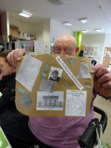 A member of Mencap Liverpool is sat holding up the poster he made which includes information and images from his archive which tell us about his life