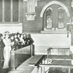 Image shows people in Victorian dress signing during a church service