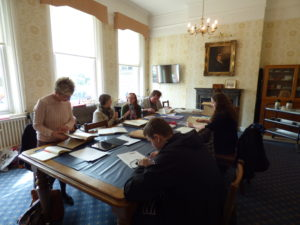 Members of the Liverpool volunteer research group are all sat around a large (seating available for at least twenty people), old fashioned (wood with a leather tabletop) table in the Royal School for the Blind boardroom. They are each exploring text based documents like newspapers, ledgers and letters. On the wall at the head of the table is a framed portrait of Edward Rushon who was one of the origibnal founders of the school.