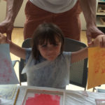Small girl shows off her monoprints from workshop