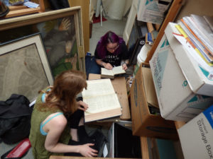 image shows two women sitting on the floor surrounded by files and paintings and looking in reference books