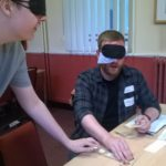 A man with a mask over his eyes plays dominos