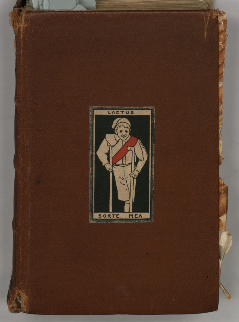 Brown leather book showing picture of boy with crutches and a red sash with laetus sorte mea written around him (happy in my lot)