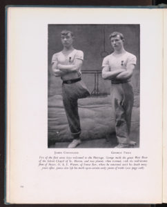 Two young men with arms folded, one with one trouser leg pinned up.