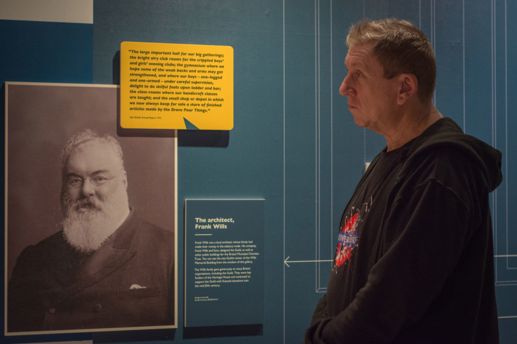 Museum visitor looks at picture of Edwardian with beard and double breasted suit