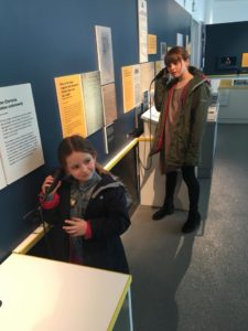 Two young archaeologists stand in The Blind School exhibition holding seakers to their ears to hear the audio description tour