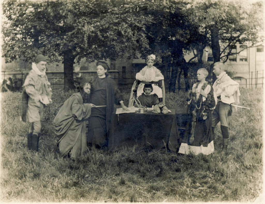The image shows a blank and white photographs of students dressed in costumes peforming a play