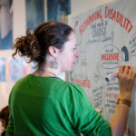 Woman in green jumper draws picture minutes for our symposium in Liverpool