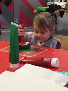 A young person is sitting at a table concentrating on rolling green paint across an acrylic board ready to make a print