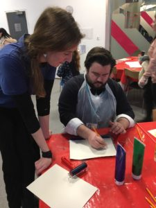 Fae Kilburn is a visually impaired artist and printmaker who is standing next to a table showing Matt Exley, Education Manager at Museum of Liverpool, how to make a print
