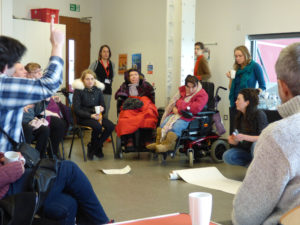 circle of disabled people discuss the mshed exhibition with grace