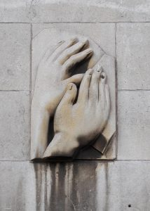 Relief sculpture from the Royal School for the Blind in Liverpool showing two hands reading braille.