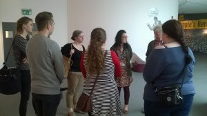 a group of people stand in a circle at a gallery entrance
