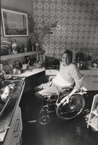 Woman in wheelchair in 70s kitchen