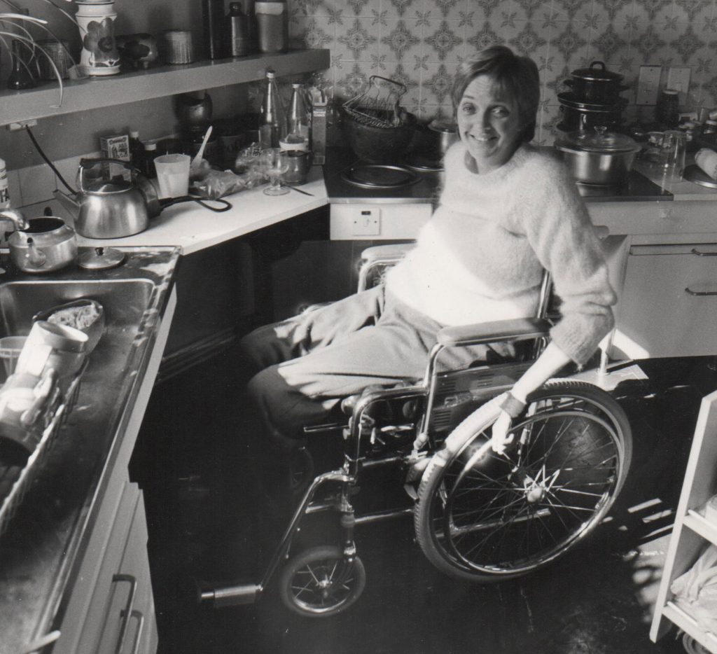 Woman in wheelchair in 70s kitchen