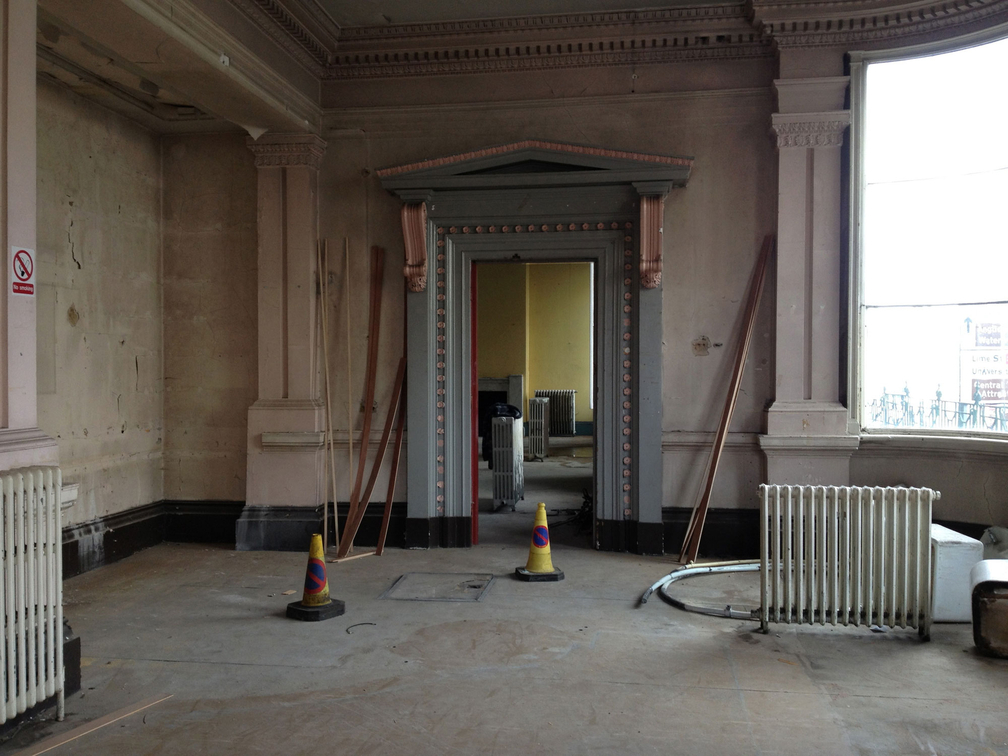 Building under renovation, slightly less peeling paint and a radiator and two cones in the middle of the floor as the regeneration progresses.