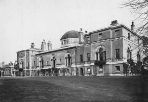 Black and white photo shows imposing long frontage of stately house with arched windows.