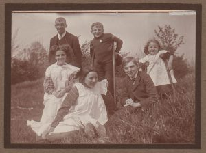 Girls in pinafores with boys and two adults in the countryside
