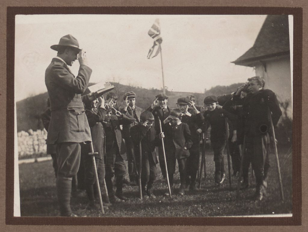Man in Scout dress and boys with crutches with a union jack in a garden