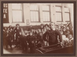 Large group of people with young boy in the foreground - large windows at the side of the hall