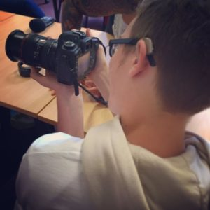 A young person is shown from behind. In his hands is a camera.