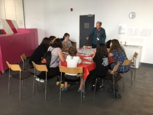 Participants are seated around a table sharing ideas in a group conversation